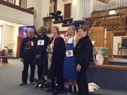 Liberal's International Pancake Day winner, Summer Parsons (center), holds the Olney Hymnal, her gift from Olney, England, which she has just received from Olney representatives Tony and Viv Evans (far left and far right). The Evanses presented the hymnal to Parsons immediately following the shriving service on Pancake Day.