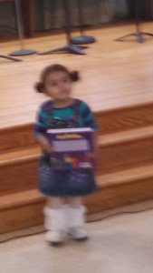 A child from Alpha y Omega receives a copy of  Resplandece