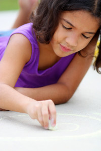 Girl in her driveway playing with chalk
