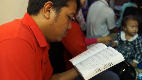 Youth leader Ngun Du Sang sings from his hymnal during a Saturday evening prayer meeting at another Chin Emmanuel congregation member's house (Houston, TX).